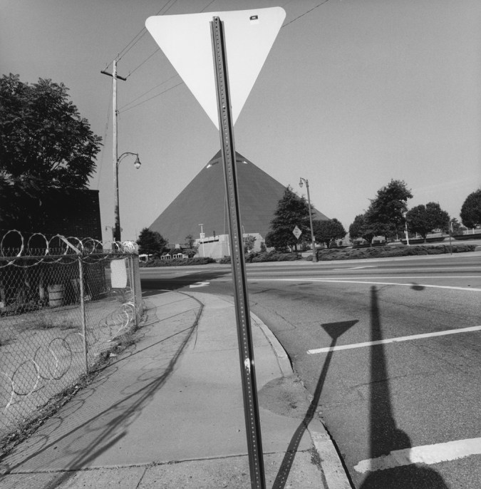A black and white photograph of the back of a yield sign lined up with a pyramid in the distance