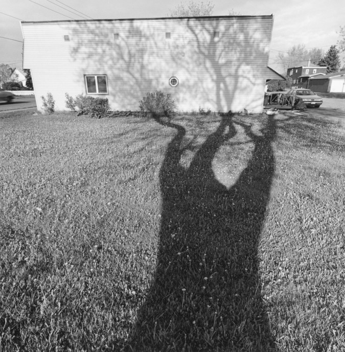 A black and white photograph of a self portrait of the shadow of a tree against a house