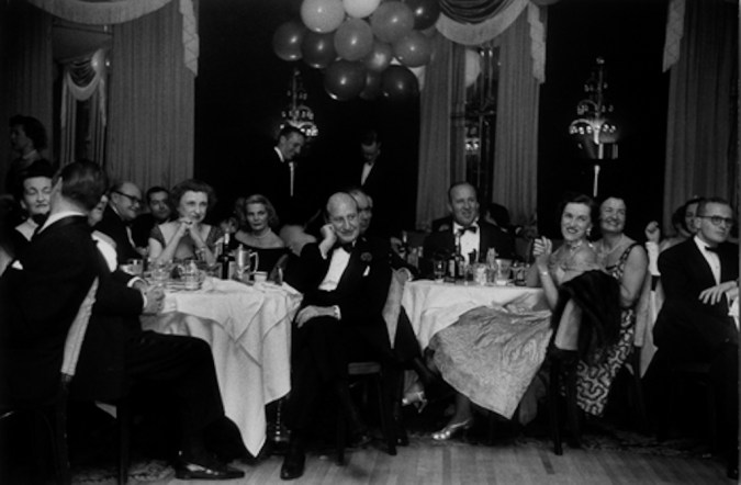Black-and-white photograph of a party setting with men and women in formal dress seated at round tables