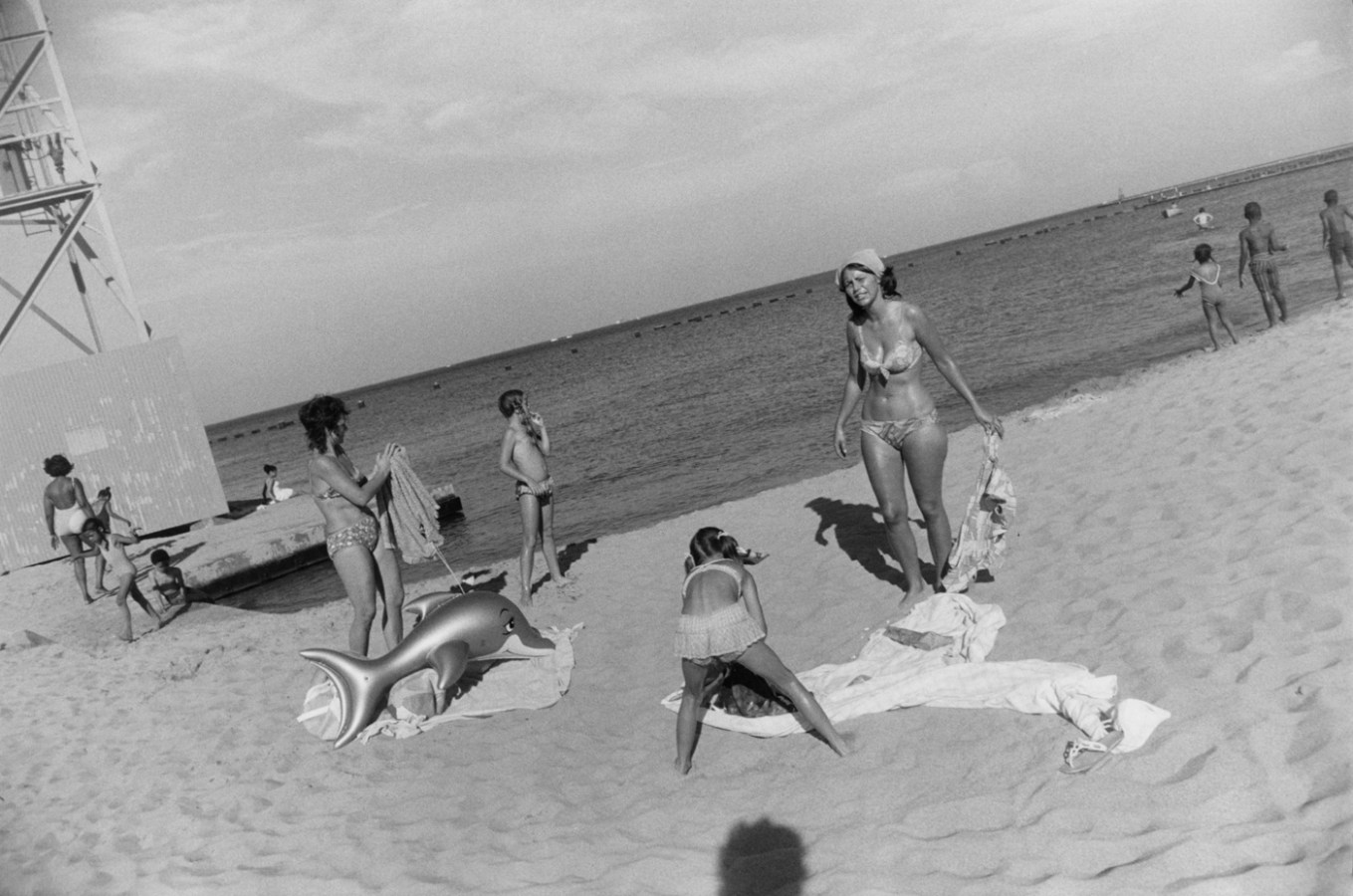 Black-and-white photograph of a group of people in swimsuits on the beach