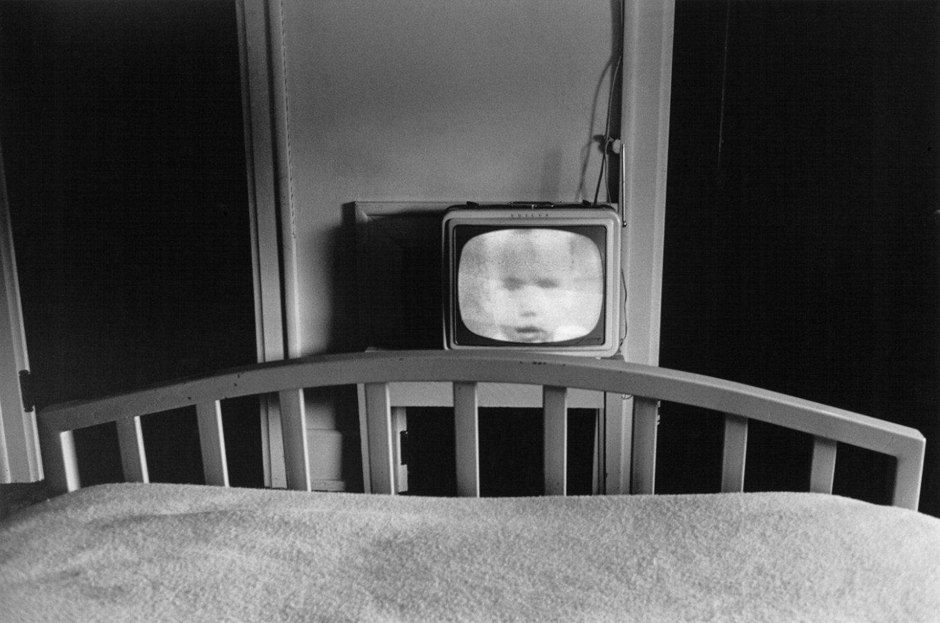 Black-and-white photograph of the bottom edge of a bed and a television with a childs face on screen