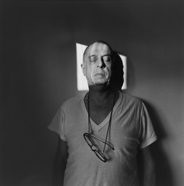 A black and white photograph of a self portrait of the artist with a square beam of light on his face