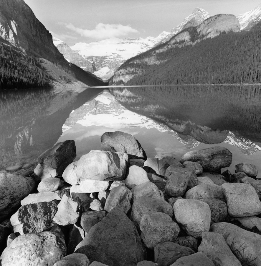 Black-and-white photograph of mountains and a lake and rocks in the foreground