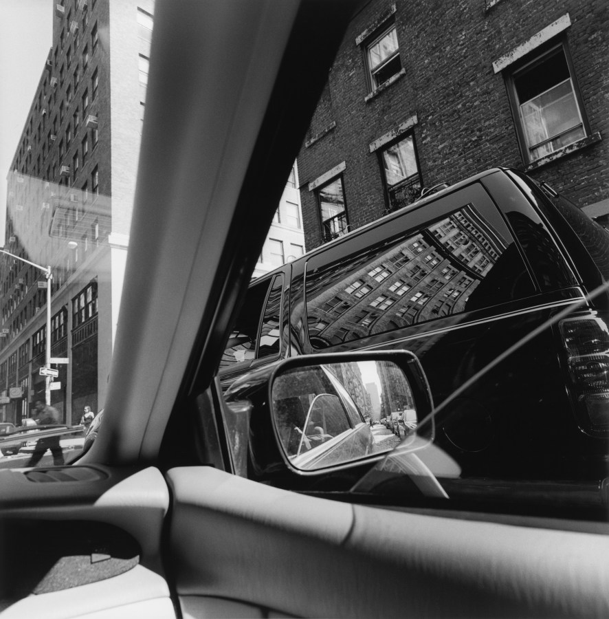 Black and white photograph out the window of a car of a reflection on a parked car