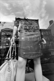 Black and white photograph of a mannequin in a storefront with the reflection of the buildings across the street in the glass window