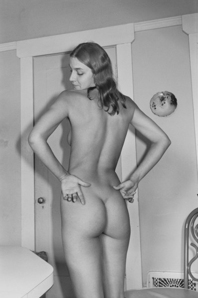 A black and white photograph of a nude woman with her back to the camera