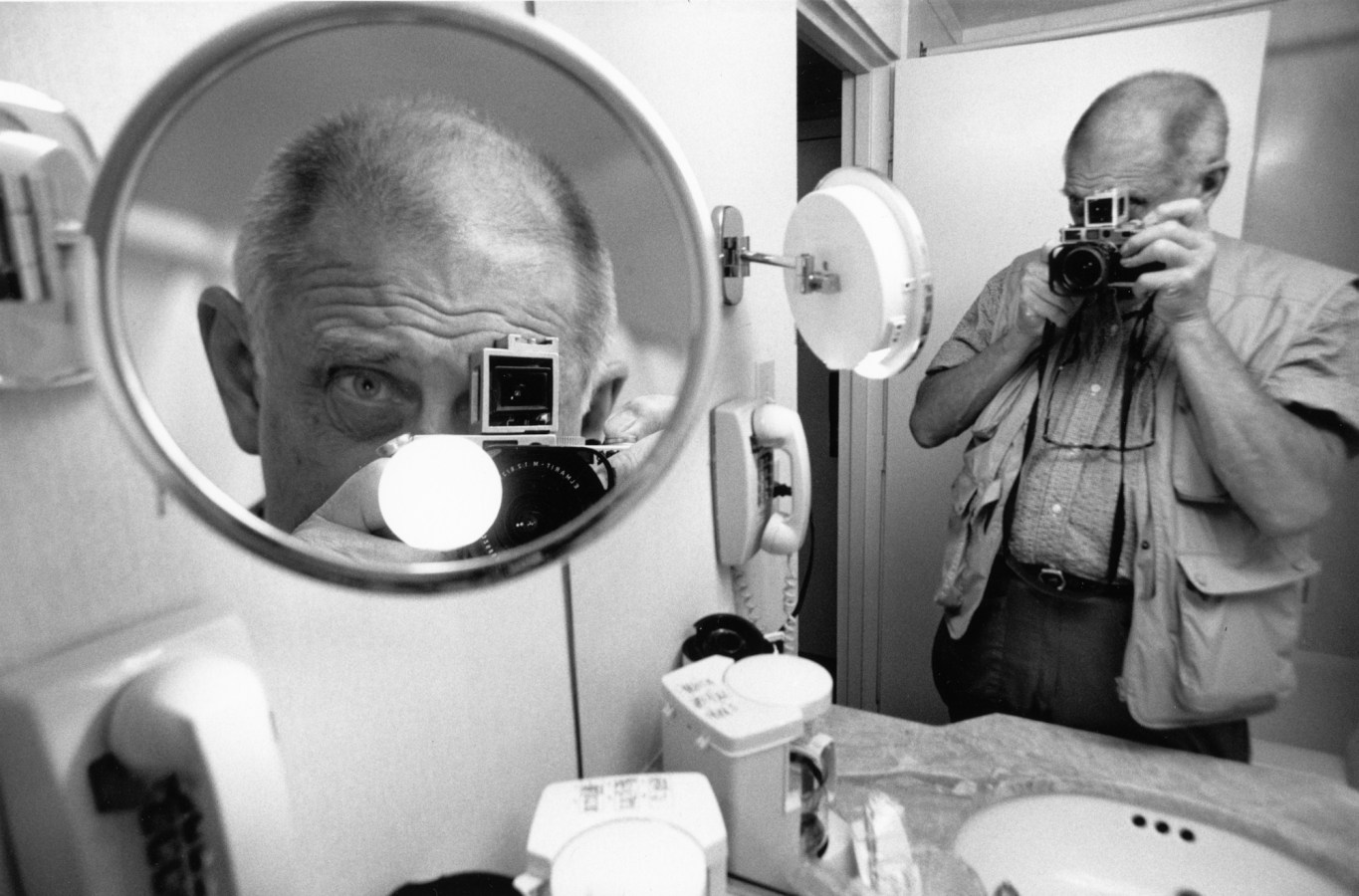 A black and white photograph of a self portrait of the artist in the reflection of two different bathroom mirrors