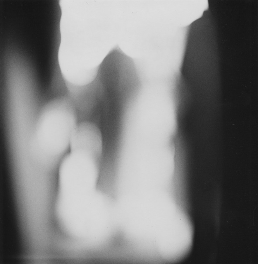 Black-and-white out-of-focus photograph of a figure standing between two dark blobs