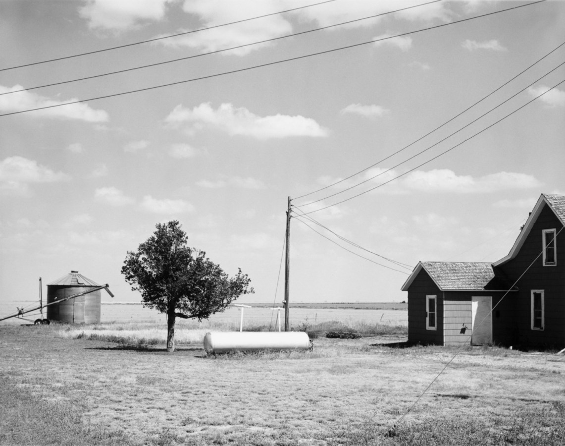 A black and white photograph of a rural building with storage tanks and a single tree, and telephone wires and scattered clouds in the sky.