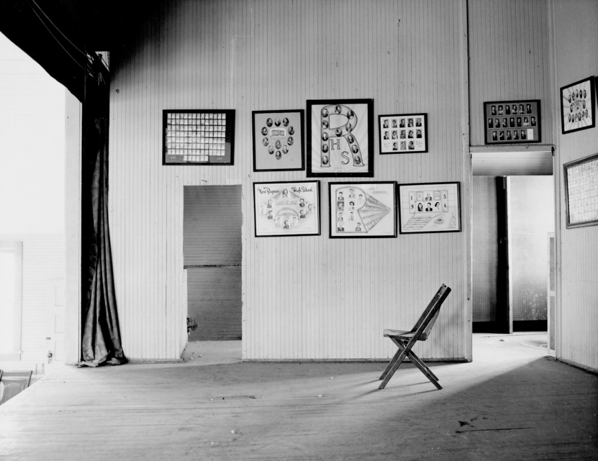 An empty stage with multiple framed photographs of graduating students, a curtain at the left side of the image and single wooden folding chair at right side of the image.
