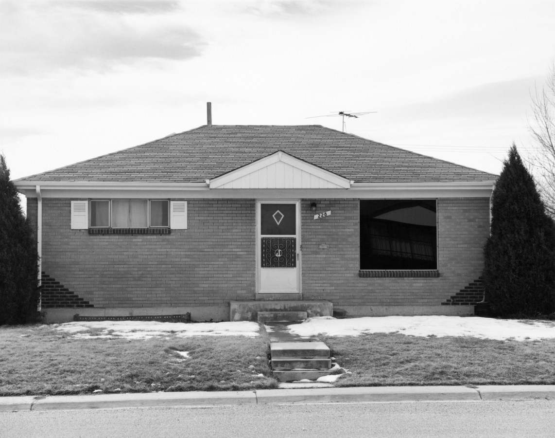 A black and white photograph of a suburban house.