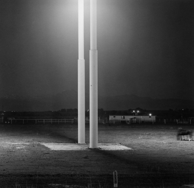 Black-and-white photograph of two illuminated metal poles at night