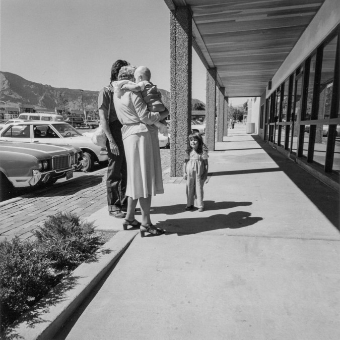 Black-and-white photograph of a man and woman holding a child with their backs to the camera, another child facing the camera. Parked cars and storefronts are in the background.