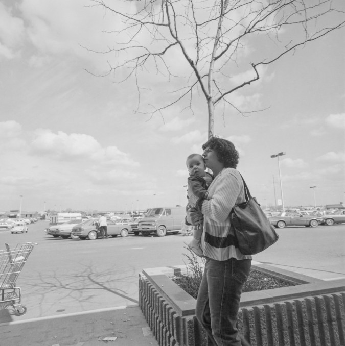 Black-and-white photograph of a woman holding a baby, in the background is a tree with no leaves in the center, a shopping cart to the left, and a parking lot filled with cars