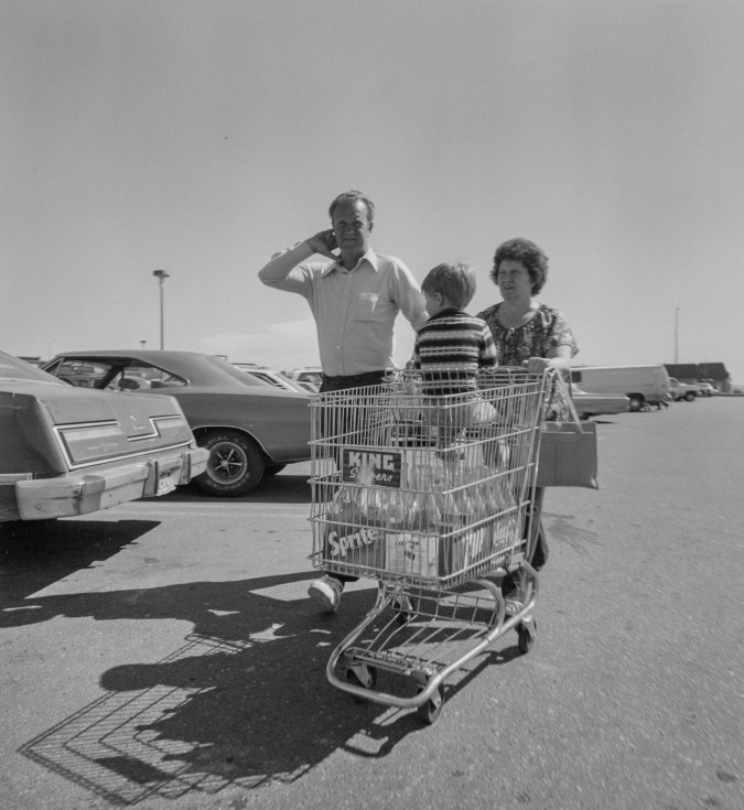 Black-and-white photograph of a man and woman pushing a shopping cart containing a child and cases of Sprite soda through a parking lot filled with cars.