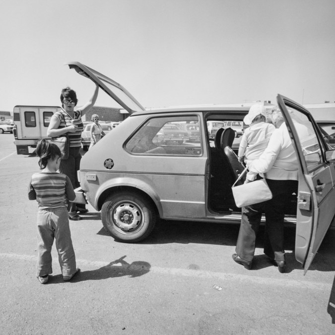 Black-and-white photograph of two women and two children loading items into a Volkswagen hatchback car, a woman wearing sunglasses watches from the background