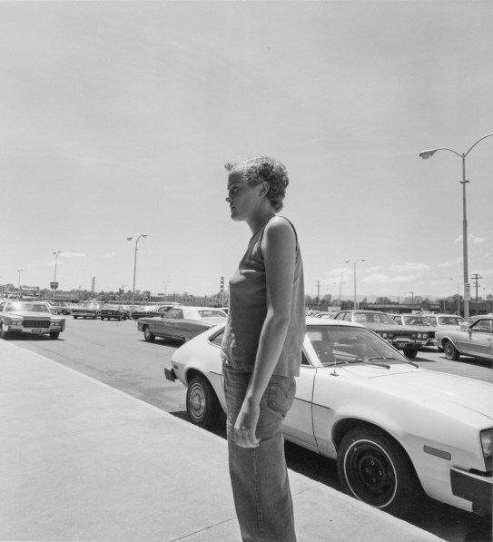 Black-and-white photograph of a person looking to the left in front of a parking lot filled with cars