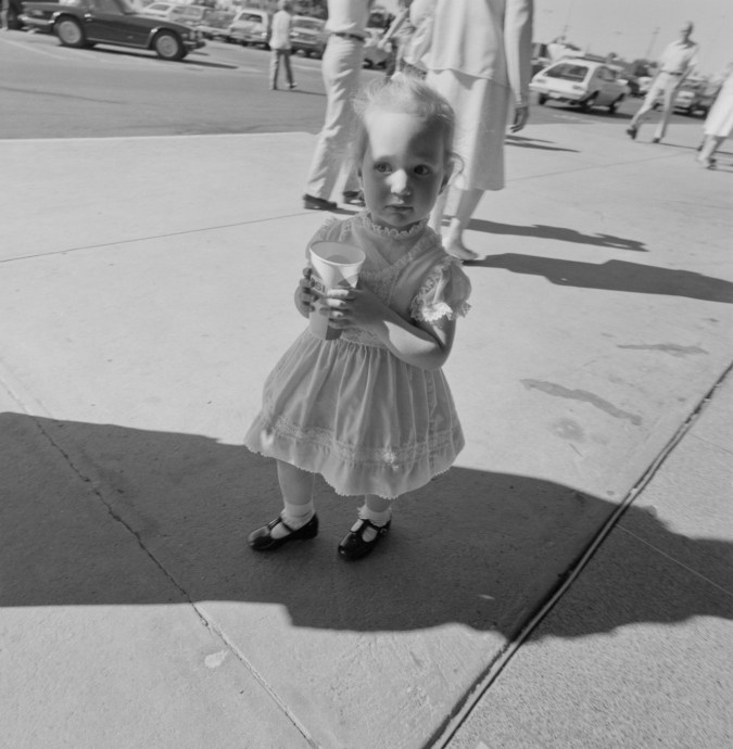 Black-and-white photograph of a young girl holding a paper cup in the shadow of another person with figures in the background