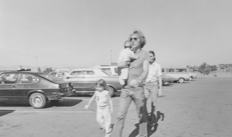 Black-and-white photograph of a family walking through a parking lot filled with cars