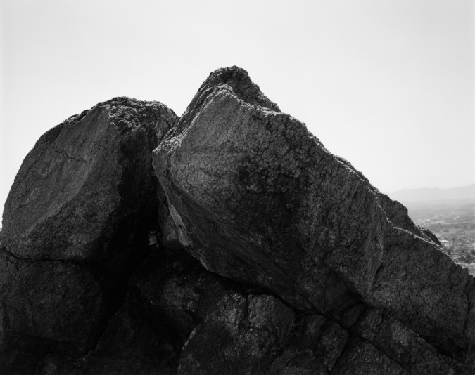 Black-and-white photograph of a rock formation against a bright clear sky