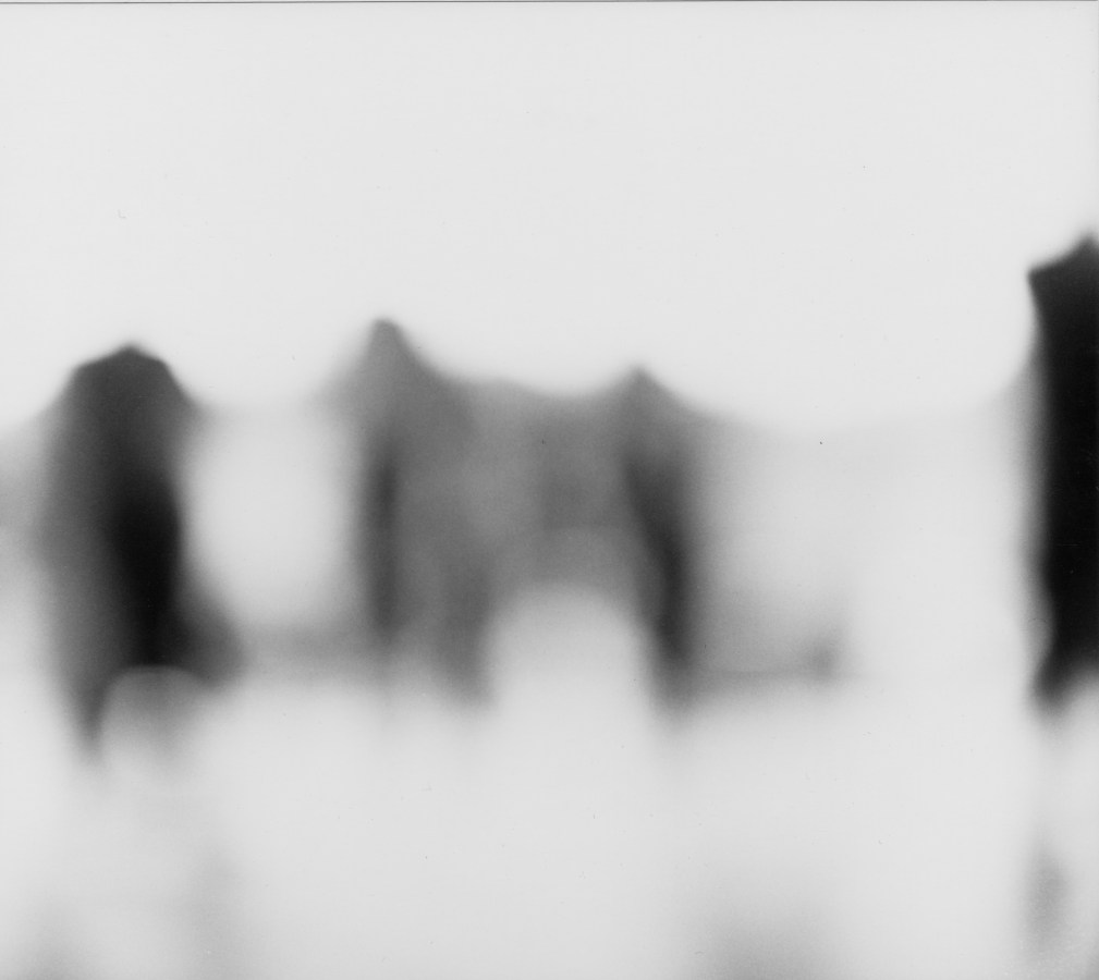 Black and white photograph of blurred dark figures