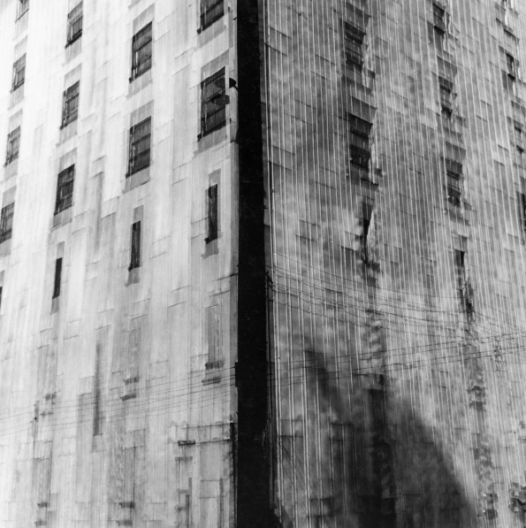 Black-and-white multiple-exposure photograph of the corner of a tall city building with evenly spaced rectangular windows