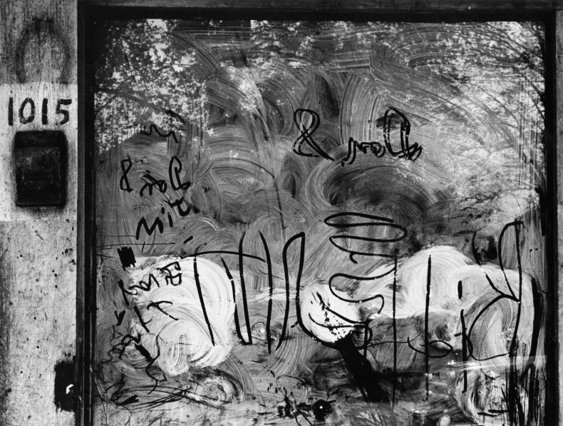 Black-and-white photograph of a soaped-up window with squiggles and letters drawn into it