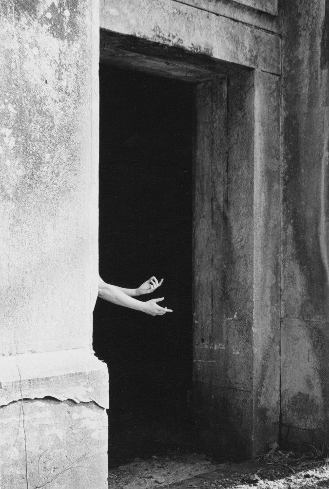 Black-and-white photograph of a person's outstretched forearms through a darkened stone archway