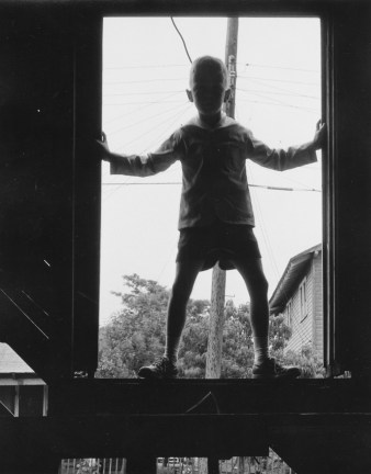 Black-and-white photograph of a young boy standing in a window frame