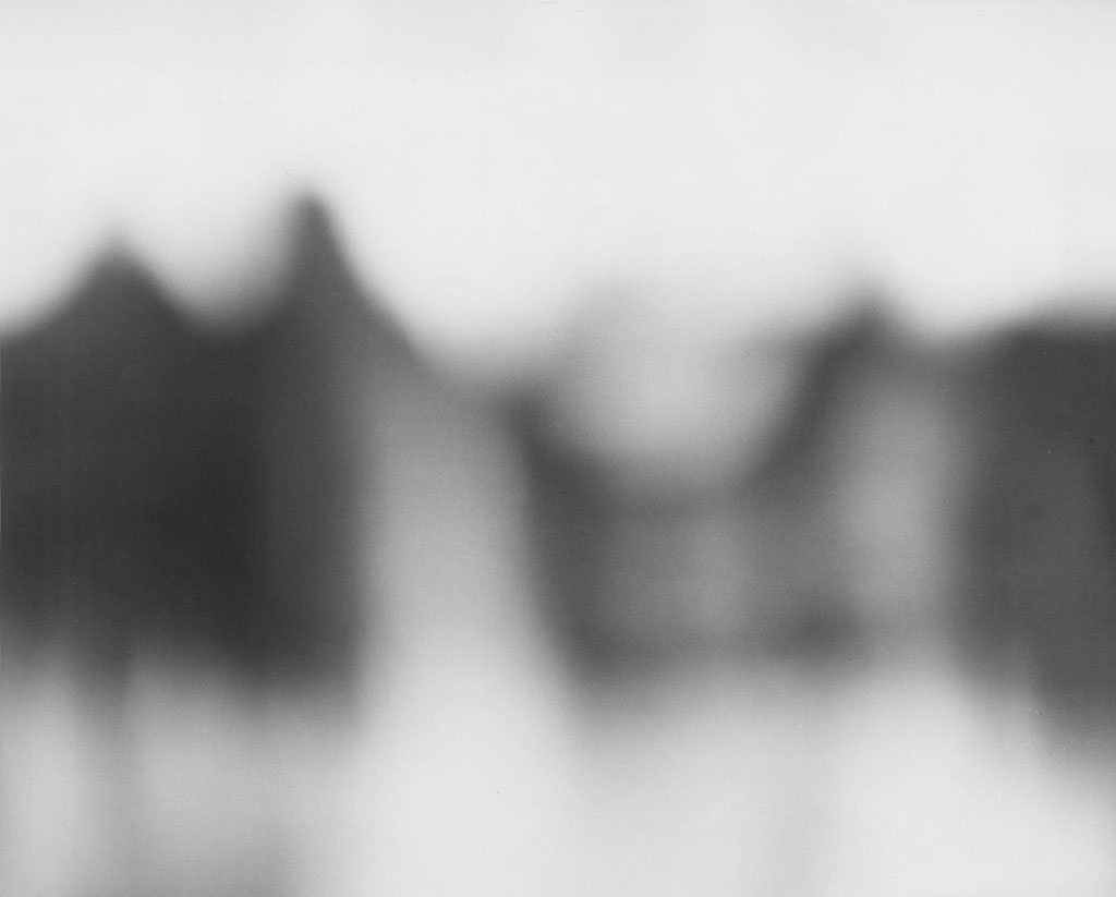 Black-and-white out-of-focus photograph of three or four dark standing figures on a light background