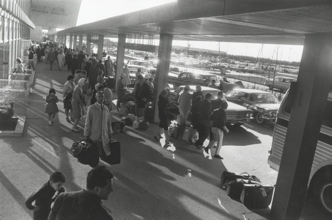 Black-and-white photograph of a sidewalk with passengers and luggage next to a narrow road with two lanes of cars