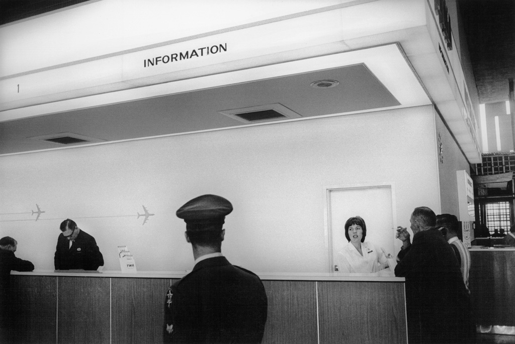 Black-and-white photograph of a pilot passing in front of an information desk staffed by a man and a woman