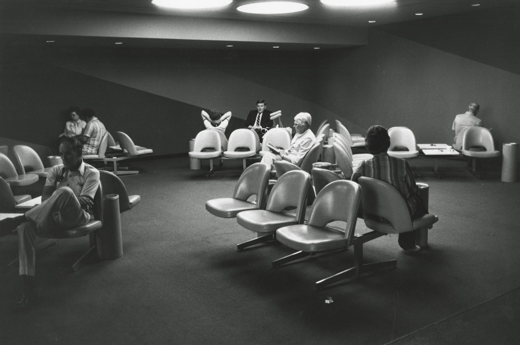 Black-and-white photograph of a waiting area with passengers scattered among seats