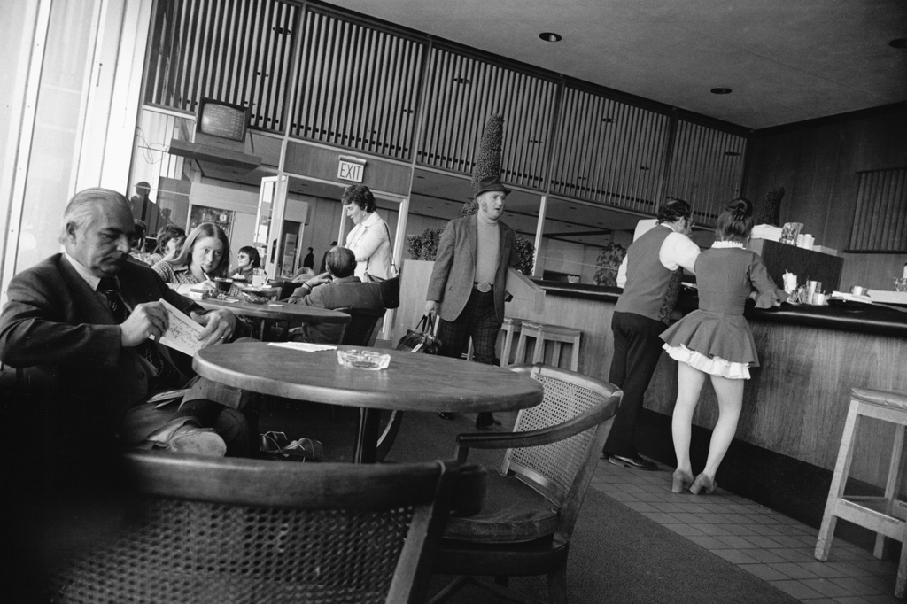 Black-and-white photograph of a man passing through a cafe area surrounded by tables and a counter