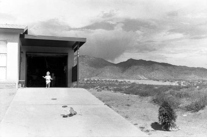 Black-and-white photograph of a toddler emerging from an open garage door against a mountainous desert landscape