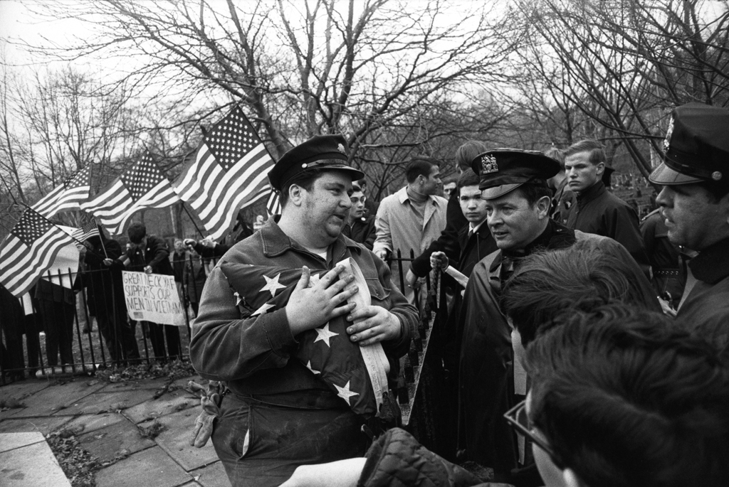 Black-and-white photograph of a man holding a folded American flag conversing with people across a fence