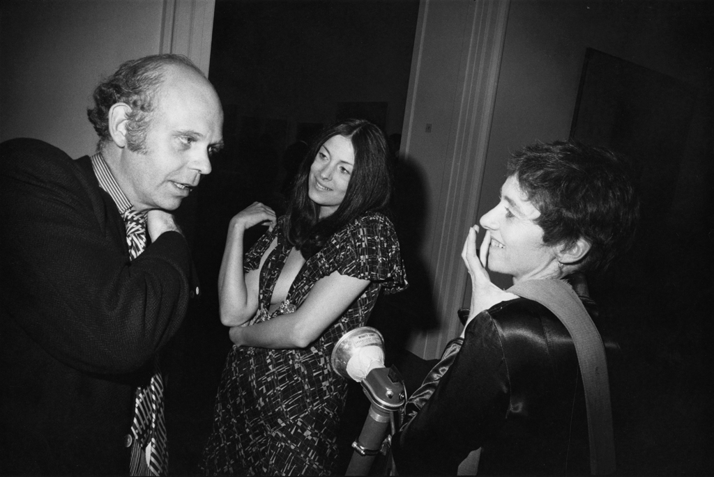 Black-and-white photograph of a man speaking to two smiling women