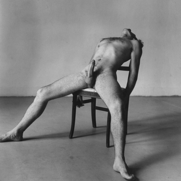 Black-and-white photograph of a seated nude man with an erection bending backward in his chair