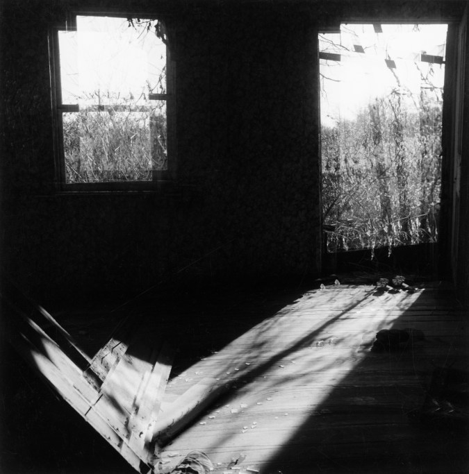 Black-and-white multiple-exposure photograph of sunlight entering a dark room through two windows