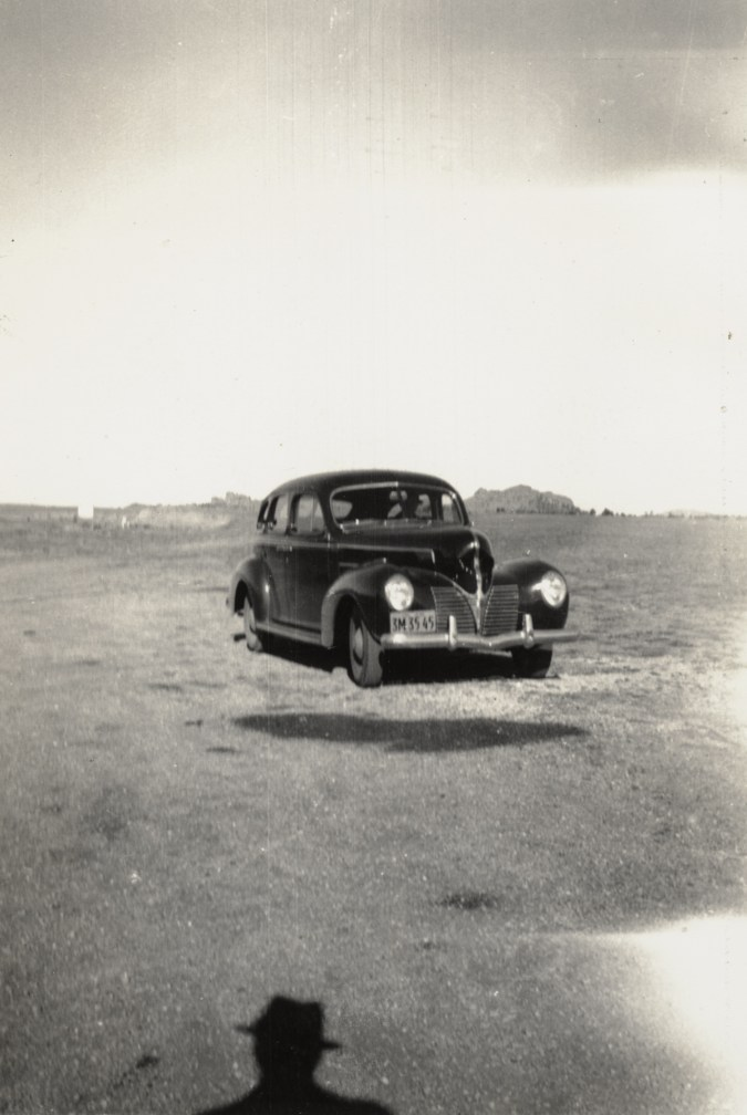 Black and white photograph of an early car in an empty landscape with the photographer's silhouette on the ground