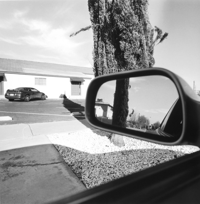 Black and white photograph of a car's side mirror reflecting a suburban settting