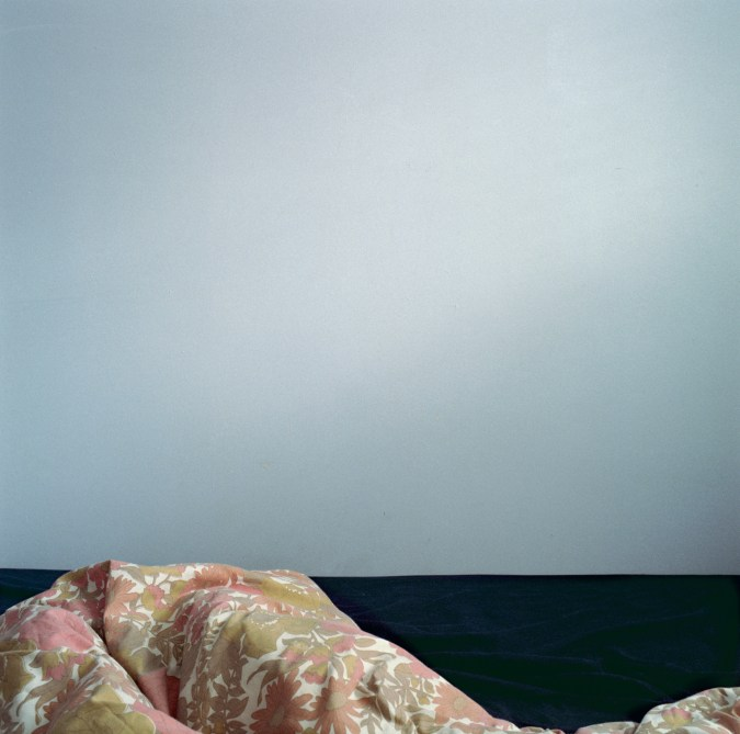 Color photograph of an umade bed in front of a blue wall.