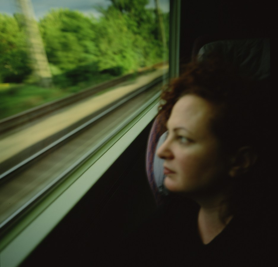 Color photograph of a woman looking out of a moving train window