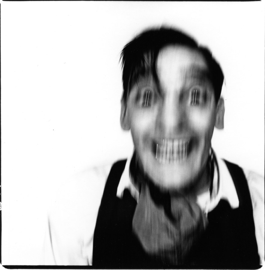 Black and white photograph of a person's grinning face in motion