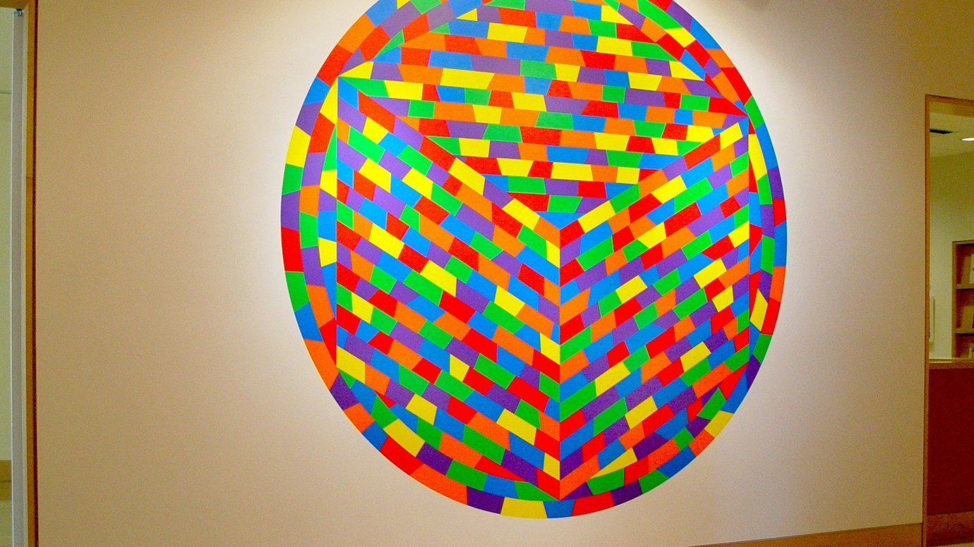 Installation photograph of a wall drawing of tessellating rainbow trapezoids inscribed in a circle