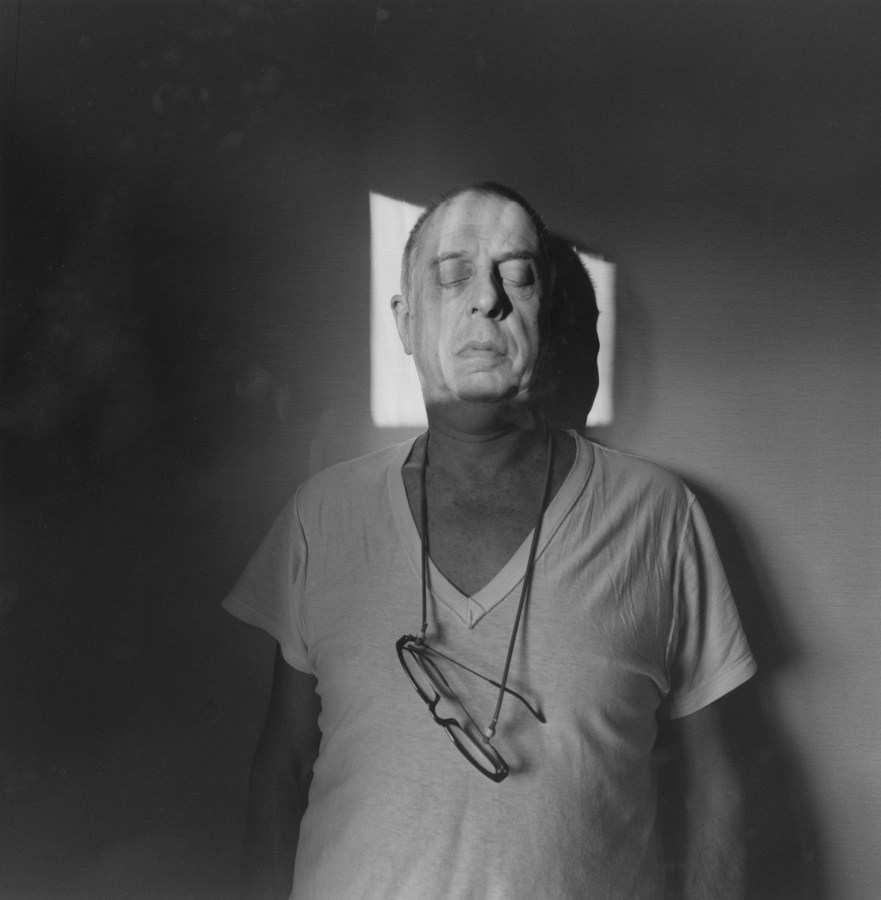 A black and white self portrait of Lee, up against a wall with his eyes closed, his head in a square of light.