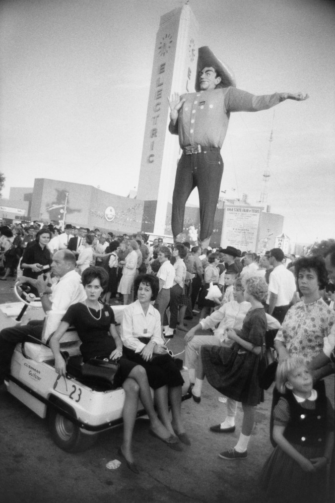 Black and white photograph of a crowd standing beneath a large statue of a man in front of an electric building