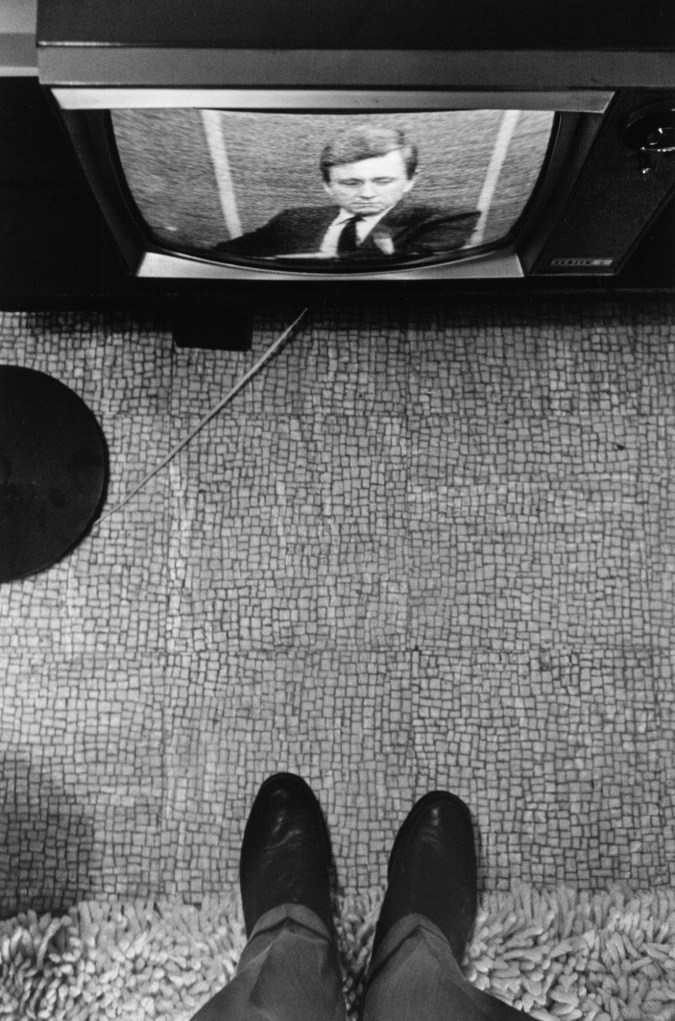 Black and white photograph of a person's shoes and a television screen displaying a newscaster