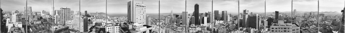 Black and white panoramic photograph of a cityscape dotted with high rises