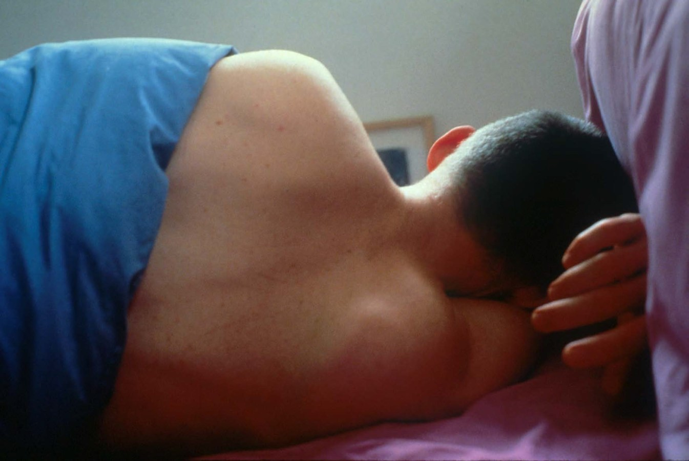 Color photograph of a person in bed with their back to the viewer